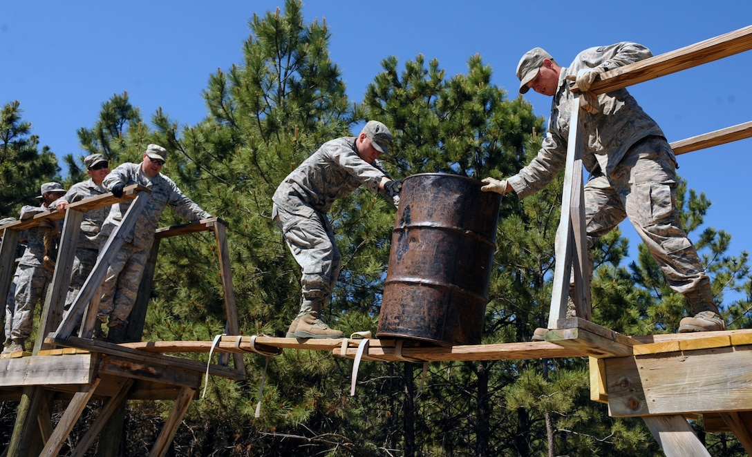 Staff Sgt. David Loving, 28th Civil Engineer Squadron structures apprentice, center, prepares to pass an oil drum to Senior Airman Kurt Nelson, 28th CES structures apprentice during a leadership reaction course at the South Dakota National Guard West Camp Rapid training facility, Rapid City, S.D., June 17, 2016. The course included over 10 different obstacles designed to build and strengthen team cohesion and communication skills. (U.S. Air Force photo by Airman 1st Class Denise M. Nevins/Released)