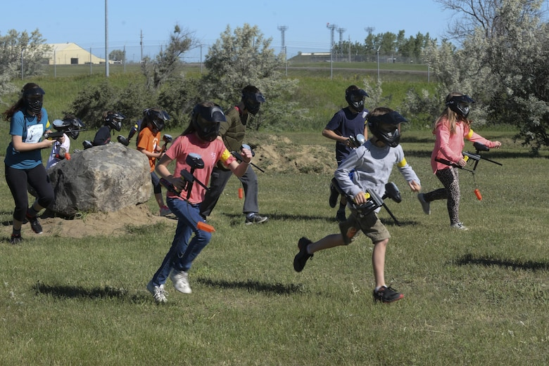 Children from the youth center at Minot Air Force Base, N.D., run toward their opponent during Paintball 101 June 17, 2016. This course was offered as a week-long summer camp for all members of the youth center. (U.S. Air Force photo/Airman 1st Class Jessica Weissman)