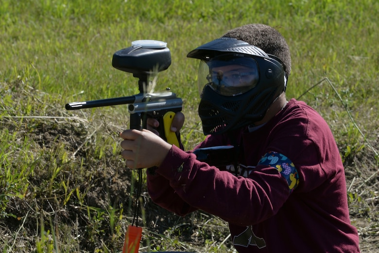 Khai Eshenko, a member of the youth center at Minot Air Force Base, N.D., aims toward his opponent during Paintball 101 June 17, 2016. This program was offered through the summer camps program to teach children the basics of paintball.  (U.S. Air Force photo/Airman 1st Class Jessica Weissman)
