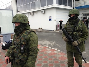 "A group of unmarked soldiers conduct a routine patrol at the Simferopol Airport in Crimea. These ""little green men,"" as they were referred to by the media, were later identified as members of the Russian armed forces."