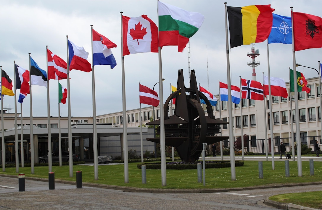 The flags of the 28 NATO member countries flap in the wind in front of headquarters in Brussels.