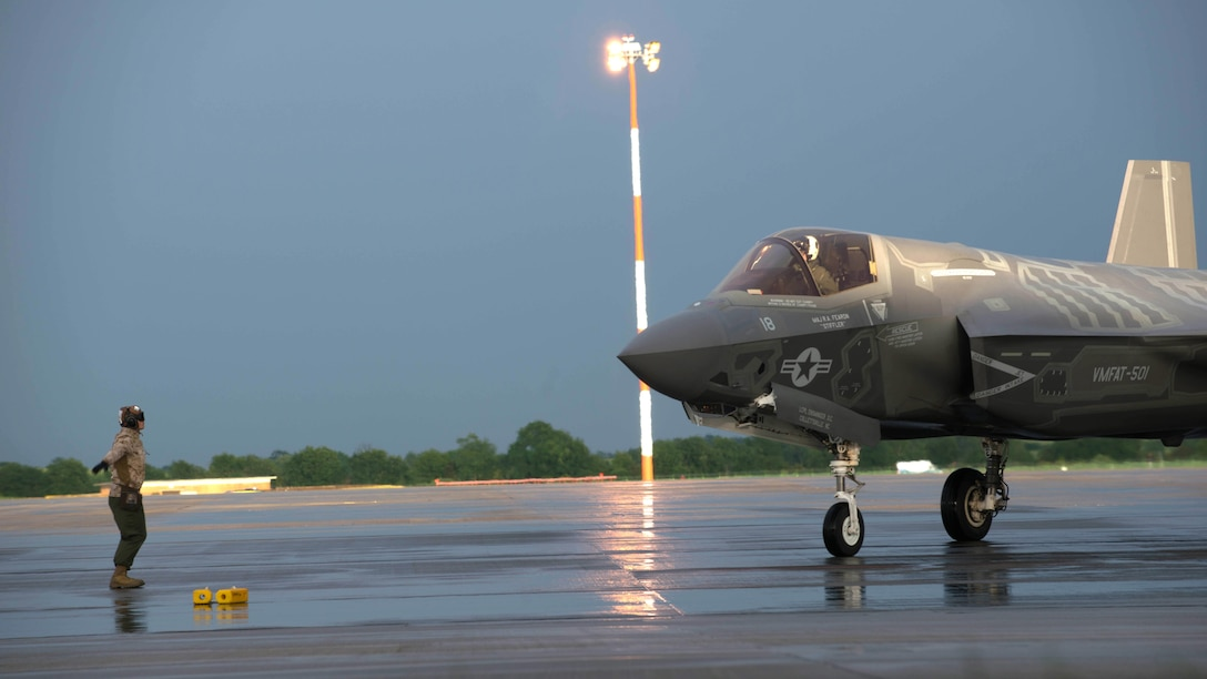 A Marine guides an F-35B Lightning II at Royal Air Force Base Fairford in the United Kingdom after the first F-35 trans-Atlantic flight, June 29, 2016. Three F-35B's flew from Marine Corps Air Station Beaufort, South Carolina and landed at RAF Fairford in Gloucester, England. They were assisted by two KC-10's and refueled 15 times over the Atlantic Ocean.