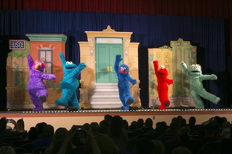 Sesame Street characters dance and sing during the USO Sesame Street Experience for Military Families held at the Sunset Cinema, aboard Marine Corps Air Ground Combat Center, Twentynine Palms, Calif., June 22, 2016. (Official Marine Corps photo by Cpl. Thomas Mudd/Released)