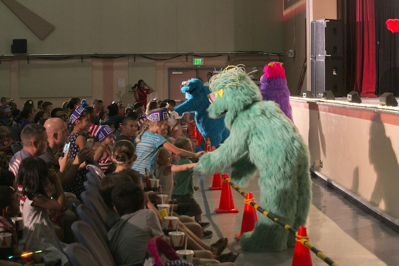 Sesame Street characters interact with children in the audience during the USO Sesame Street Experience for Military Families held at the Sunset Cinema, aboard Marine Corps Air Ground Combat Center, Twentynine Palms, Calif., June 22, 2016.(Official Marine Corps photo by Cpl. Thomas Mudd/Released)