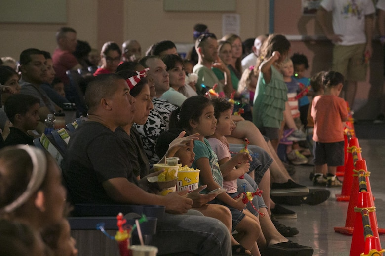 Combat Center families watch Sesame Street characters sing and dance during the USO Sesame Street Experience for Military Families held at the Sunset Cinema, aboard Marine Corps Air Ground Combat Center, Twentynine Palms, Calif., June 22, 2016. (Official Marine Corps photo by Cpl. Thomas Mudd/Released)