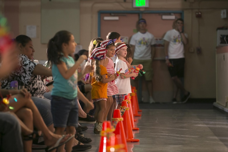 Combat Center children dance along with Sesame Street characters during the USO Sesame Street Experience for Military Families held at the Sunset Cinema, aboard Marine Corps Air Ground Combat Center, Twentynine Palms, Calif., June 22, 2016. (Official Marine Corps photo by Cpl. Thomas Mudd/Released)