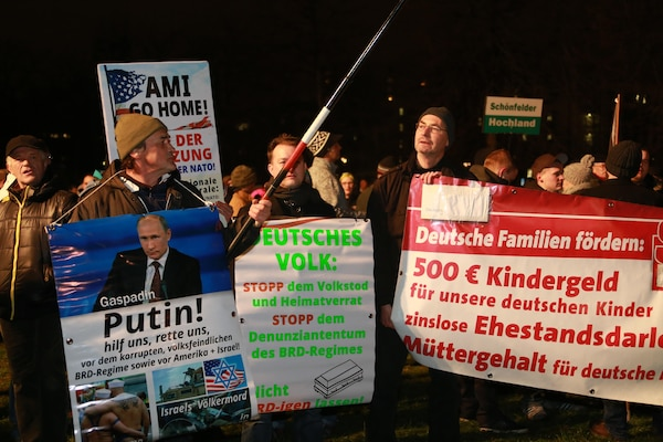 "January 2015 PEGIDA demonstration in Dresden, Germany. One protester (left) holds sign appealing to Russian President Vladimir Putin: ""Putin! Help us, save us from the corrupt, enemy-of-the-people BRD [Federal Republic of Germany] regime and from America and Israel!"""