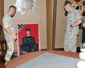 Both Col Eggers and LtCol Logan look over the plaque that LtCol Logan was presented at his retirement ceremony in honor of 24 years of faithful service