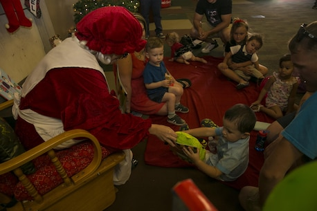 Mrs. Claus reads a book to children at the Armed Services YMCA's first Christmas You Missed event held at building 1707 aboard the Marine Corps Air Ground Combat Center Twentynine Palms, Calif., June 25, 2016. (Official Marine Corps photo by Lance Cpl. Dave Flores/Released)