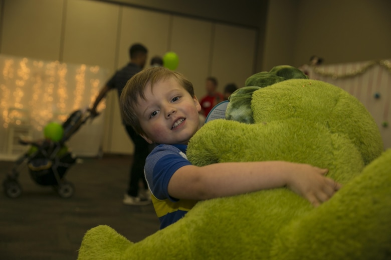 Leo Stainbrook, 3, son of Sgt. Kyle A. Stainbrook, platoon sergeant, 1st Battalion, 7th Marine Regiment, carries the new stuffed dinosaur he received from Santa Claus during the Armed Services YMCA's first Christmas You Missed event at building 1707 aboard the Marine Corps Air Ground Combat Center Twentynine Palms, Calif., June 25, 2016. (Official Marine Corps photo by Lance Cpl. Dave Flores/Released)