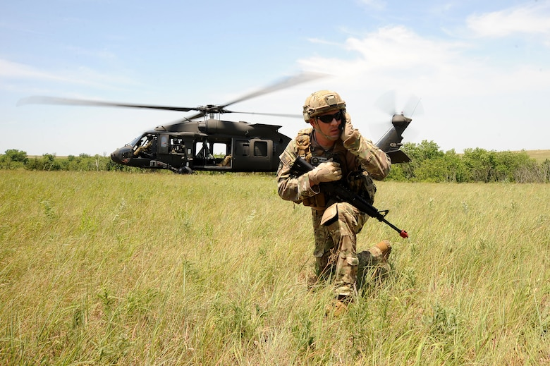 Master Sgt. Benjamin Jenkins, 10th Air Support Operations Squadron, chief joint terminal attack control instructor, communicates with aircrew in front of a UH-60 Blackhawk, June 22, 2016, at Fort Riley, Kan. JTACs provide Air Force support by planning and controlling combat air resources and operating communications in support of Army ground maneuver units. (U.S. Air Force photo/Airman 1st Class Jenna K. Caldwell)