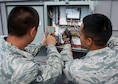 Staff Sgt. Dads Zyron Maniego, 99th Civil Engineer Squadron Heating, Ventilating, and Air Conditioning technician, and Senior Airman Octavio Nila 99th CES HVAC technician, check readings on an A/C unit atop of the Base Exchange on Nellis Air Force Base, Nev., June 28, 2016. With HVAC Controls only having a little over 30 Airmen able to support the base's needs, customers may experience wait times when HVAC responds to emergency calls which can include the Base Exchange.