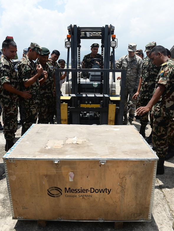 Tech. Sgt. Derrick McCall, 36th Contingency Response Group, demonstrates how to lift an object as a member of the Nepalese Army operates a forklift June 28, 2016, at Tribhuvan International Airport in Kathmandu, Nepal. Ten Airmen from the 36th CRG and more than 20 service members from various Nepalese organizations participated in a subject-matter expert exchange where participants familiarized themselves with operating a forklift and learned techniques on transporting cargo. (U.S. Air Force photo by Staff Sgt. Benjamin Gonsier/Released)