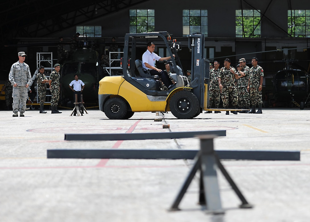 Madhu Sudan, Civil Aviation Authority of Nepal, drives a forklift through an obstacle course during a subject-matter expert exchange on cargo handling June 28, 2016, at Tribhuvan International Airport in Kathmandu, Nepal. T'he obstacle course tested a forklift operators' ability to navigate around obstacles as safely as possible. (U.S. Air Force photo by Staff Sgt. Benjamin Gonsier/Released)