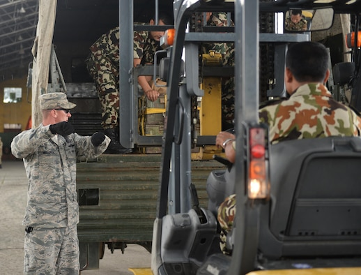 Tech. Sgt. Randy Walgren, 36th Contingency Response Group, signals to a forklift operator to lower the forks as cargo is prepared for transport during a subject-matter expert exchange June 29, 2016, at Tribhuvan International Airport in Kathmandu, Nepal. Participants of the SMEE exchanged knowledge on how each organization operates a forklift and the different hand signals they use to communicate a message. (U.S. Air