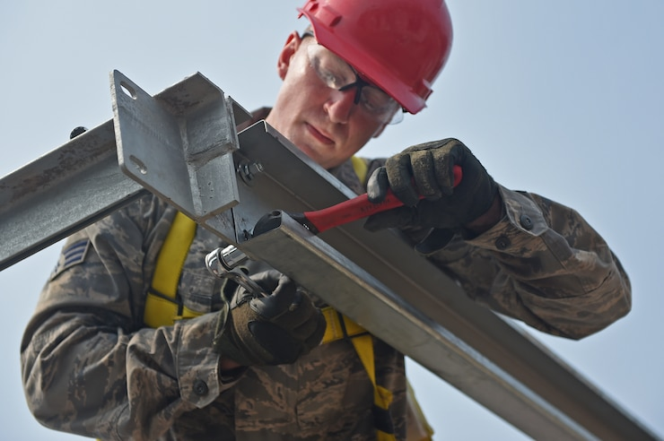 Pennsylvania Air National Guard Senior Airman Daniel Clark, 201st Rapid Engineer Deployable Heavy Operational Repair Squadron Engineers structures technician, tightens a bolt on a purlin beam as part of the construction process for a new medical clinic May 3, 2016 during Exercise BEYOND THE HORIZON 2016 GUATEMALA. The bolts that secure the purlin beam to the trusses are tightened using locking washers to keep them from loosening under stress. (U.S. Air Force photo by Senior Airman Dillon Davis)