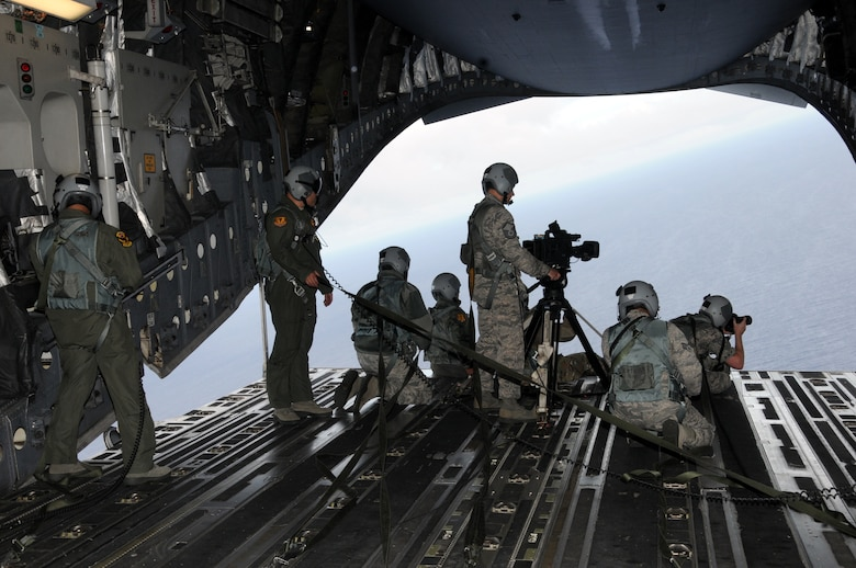 ANG Creative captures video and still imagery during an aerial photo shoot on board a 204th Airlift Squadron C-17 Globemaster, May 18, 2016, Hawaii. ANG Creative is the the Air National Guard visual information team tasked with producing video, radio, photography and graphic design for the ANG Recruiting and Retention Service of the Air Directorate at the National Guard Bureau. (U.S. Air National Guard photo by Airman Stan Pak/released)