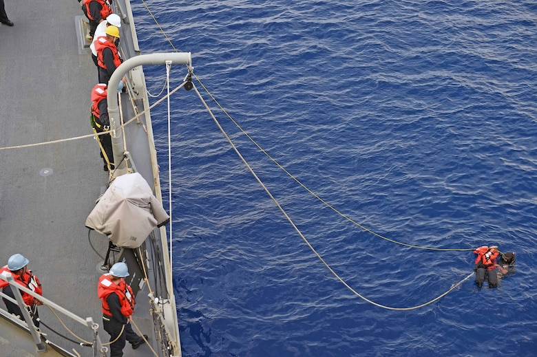 """160125-N-KM939-603 PACIFIC OCEAN (Jan. 25, 2016) - Seaman Steve Martinez, from Pueblo, Colorado, saves """"Oscar,"""" the rescue dummy, during a man overboard drill on the guided-missile destroyer USS Stockdale (DDG 106). Providing a ready force supporting security and stability in the Indo-Asia-Pacific, Stockdale is operating as part of the John C. Stennis Strike Group and Great Green Fleet on a regularly scheduled 7th Fleet deployment. (U.S. Navy photo by Mass Communication Specialist 3rd Class David A. Cox/Released)"""