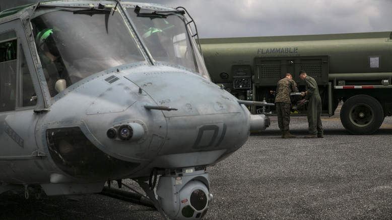 Two Marines work together to refuel a UH-1Y Huey before a flight during Exercise Cobra Gold in Utapao, Thailand, Feb. 16, 2016. Logistic and aviation units work together to practice the characteristics of a Marine Air-Ground Task Force. Cobra Gold is a multi-national exercise designed to build partnership and interoperability between participating nations. The Marines are with Marine Wing Support Squadron 172, Marine Aircraft Group 36. 1st Marine Aircraft Wing, III Marine Expeditionary Force.