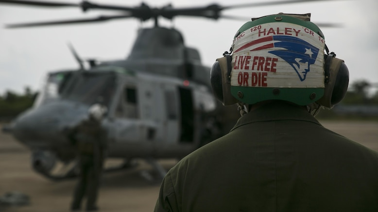 Sgt. Andrew A. Haley observes a UH-1Y Huey as it prepares to take off for a flight mission during Exercise Cobra Gold 16 in Utapao, Thailand, February 16, 2016. Haley, an avid New England Patriots fan, is one of many maintainers who help prepare aircraft before and after takeoff. Cobra Gold is a multi-national exercise designed to advance regional security and ensure effective responses to regional crises by bringing together a robust combined task force from partner nations sharing common goals. Haley, from Conway, New Hampshire, is an airframe mechanic with Marine Light Attack Helicopter Squadron 167, currently supporting Marine Aircraft Group 36, 1st Marine Aircraft Wing, III Marine Expeditionary Force as part of the unit deployment program.