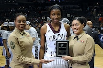 Master Sgt. Amy Romero, Marine reservist, and Capt. Evita Mosqueda-Chapman, logistics officer for 4th Tank Battalion, hand the Marine Corps Excellence in Leadership Award to Lady Walker of Virginia Union University following the women's finals game of the CIAA championships at the Time Warner Cable Arena in Charlotte, N.C., Feb. 27, 2016. Virginia Union University defeated Shaw University 70 - 66. The Marines are present at the Central Intercollegiate Athletic Association championships to spread awareness to student athletes and fans about opportunities in the Marine Corps. (Official Marine Corps photo by Cpl. John-Paul Imbody)