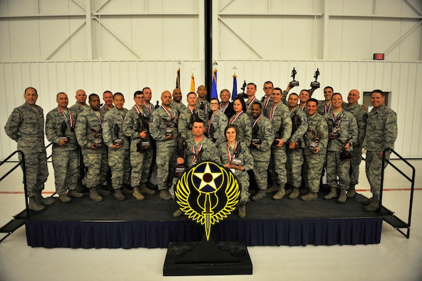 Airmen assigned to the 27th Special Operations Maintenance Group pose for a group photo with their awards and leadership during the Maintenance Professional of the Year banquet Feb. 26, 2016, at Cannon Air Force Base, N.M. The MPOY banquet is an annual event where all the squadrons within the 27th SOMXG come together to celebrate individual and team achievements. (U.S. Air Force photo/Tech. Sgt. Manuel Martinez)