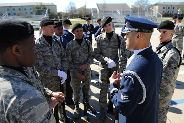 A member of the U.S. Air Force Honor Guard Drill Team speaks to technical training students following a performance on the Levitow Training Support Facility drill pad Feb. 26, 2016, Keesler Air Force Base, Miss. During the past month, the team developed the routine to be used throughout the year. (U.S. Air Force photo by Kemberly Groue)