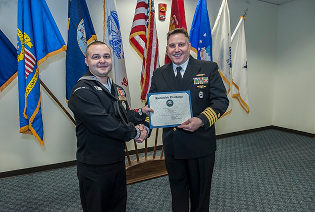 Petty Officer 2nd Class Anthony Brown reenlisted for eight more years in the Navy in a ceremony Feb. 29 presided by U.S. Navy Capt. Justin Debord, DLA Land and Maritime Chief of Staff, in Building 20.