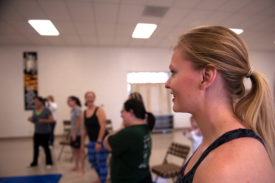 U.S. Air Force Staff Sgt. Adriene Anderson, 315th Training Squadron instructor, grins during a self-defense class at St. Marks Presbyterian Church, San Angelo, Texas, Feb. 27, 2016. Anderson initiated the Mommy Fit Camp program in August of 2015 as part of the Make Goodfellow Great Initiative for Goodfellow Air Force Base. (U.S. Air Force photo by Airman 1st Class Caelynn Ferguson/Released)