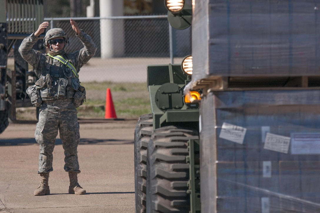 Spc. Robin Trinidad, an automated logistics specialist from the 103rd Quartermaster Company in Houston, Texas, guides a pallet of Meals Ready to Eat on Feb. 17, 2016 at Fort Polk, La. while supporting a field training. The Army Reserve unit is providing Class I supplies during the exercise in partnership with active Army units and foreign service members.  (U.S. Army photo by Sgt. Brandon Hubbard, 204th PAD)