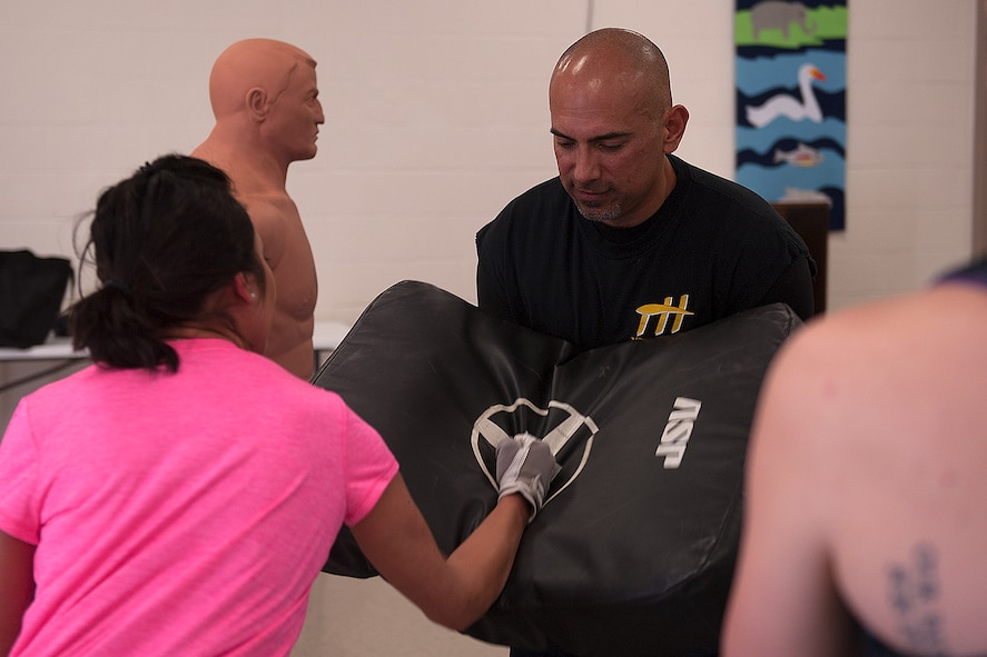 Mark E. Ledesma, 315th Training Squadron emerging technologies chief, holds a punching bag as Taylor Ledesma performs a hammer fist during a self-defense class, at St. Marks Presbyterian Church, San Angelo, Texas, Feb. 27, 2016. Mark Ledesma taught the class as an option for a workout of the Mommy Fit Camp program. (U.S. Air Force photo by Airman 1st Class Caelynn Ferguson/Released)