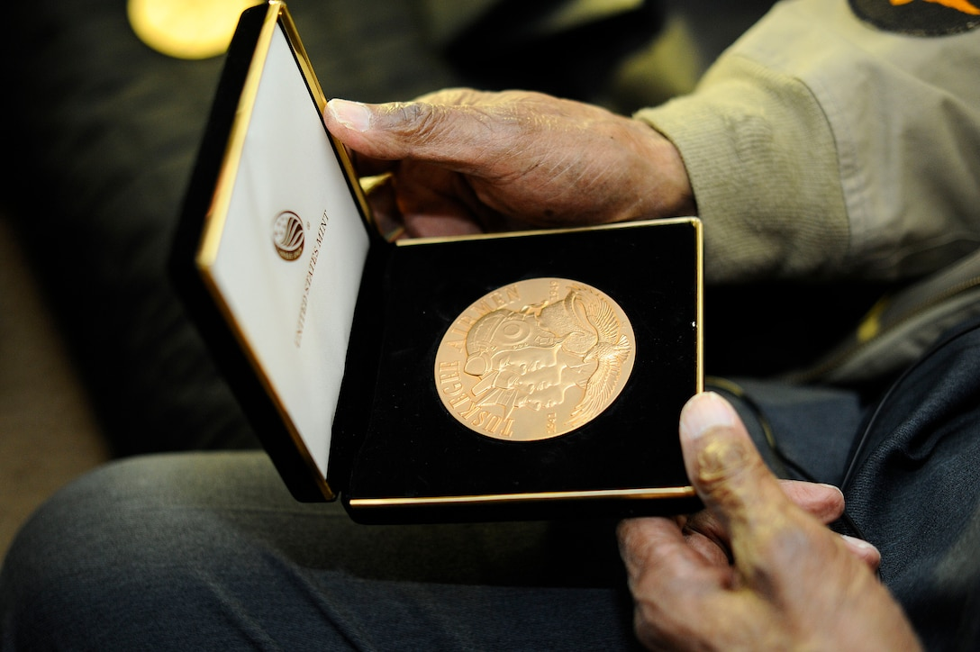 Retired Maj. George Boyd exhibits a Congressional Gold Medal at his home in Wichita, Kan., Feb. 4, 2016. Boyd is a 28-year combat veteran and member of the famous Tuskegee Airmen. Boyd received two Congressional Gold Medals, one as a member of the Tuskegee Airmen and the other as part of the U.S. Civil Air Patrol. (U.S. Air Force photo/Airman Jenna K. Caldwell)
