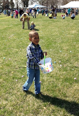 Reese King, son of U.S. Air Force Master Sgt. Rayna Lawter and U.S. Air Force Tech. Sgt. Chevy King, places an egg in his Easter egg basket during the chapel's annual Easter egg hunt April 5, 2015 at Offutt Air Force Base, Neb. In 2016 the chapel will hide 55,000 eggs on the base's parade grounds.