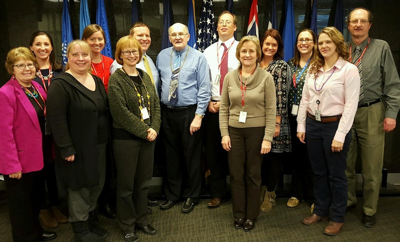 The Omaha District Office of Counsel surround the outgoing District Counsel, Rick Totten, while supporting the incoming District Counsel, and former Deputy Chief Counsel, Tom Tracy. They are from left, Linda Doll, Stacy Birkel, Alecia Dembowski, Erin Murphy, Cathy Grow, Jim Pakiz, Richard Totten, Tom Tracy, Linda Burke, Melissa Head, Amanda Lyon, Stephanie Frazier and Stan Tracey. Not shown is Tom Ingram.