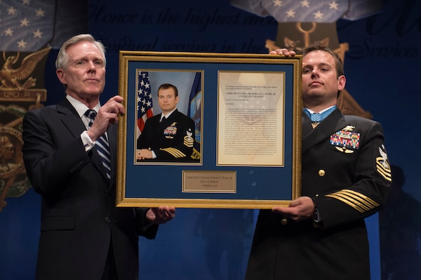 Navy Secretary Ray Mabus and Navy Senior Chief Petty Officer Edward C. Byers Jr., a Medal of Honor recipient, hold a plaque honoring Byers during a ceremony to induct him into the Hall of Heroes at the Pentagon, March 1, 2016. DoD photo by Air Force Senior Master Sgt. Adrian Cadiz