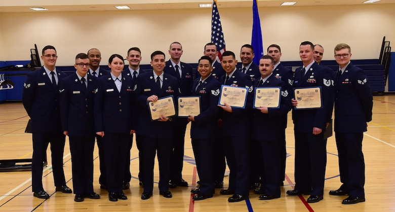 Team Buckley members stand together after being promoted to their next ranks Feb. 29, 2016, at the Buckley Fitness Center on Buckley Air Force Base, Colo. A promotion ceremony is a time-honored tradition in the Air Force, allowing co-workers, family and friends to support and congratulate Airmen on their promotion. (U.S. Air Force photo by Airman 1st Class Gabrielle Spradling/Released)