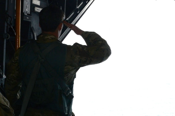 A pararescueman from the 320th Special Tactics Squadron pays his respects to the crew and passengers of Stray 59 from a U.S. Air Force MC-130H Combat Talon II off the coast of the Philippines Feb. 26, 2016. The Stray 59 memorial flight is conducted annually to honor those who were lost 35 years ago when a 1st SOS MC-130E, call sign STRAY 59, crashed during an exercise killing eight crew members and 15 passengers.  Two of the passengers were combat controllers from the 320th Special Tactics Squadron.   (U.S. Air Force photo by Master Sgt. Kristine Dreyer, 353rd Special Operations Group)