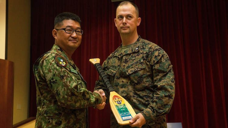U.S. Marine Corps Lt. Col. Matthew Lundgren, commanding officer, 1st Battalion, 4th Marine Regiment, 1st Marine Division, receives a plaque from Col. Yoskiyuki Goto, regimental commander, Western Army Infantry Regiment, Japan Ground Self-Defense Force, at Marine Corps Base Camp Pendleton, California, March 1, 2016, during the closing ceremony of Exercise Iron Fist 2016. Exercise Iron Fist is an annual, bilateral amphibious training exercise conducted by the USMC and JGSDF is designed to improve their ability to conduct combined amphibious operations. The ceremony concluded the 11th iteration of the exercise, which will continue to provide unique opportunities for the U.S. Marines to train with their Pacific ally on U.S. soil.