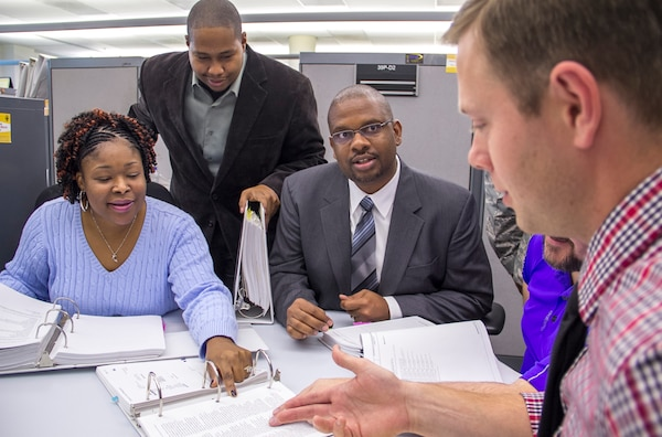 DLA Energy Bulk Petroleum Deputy Director Gerald Tinner (center) and his team discuss a current fuel project. Tinner and his team played a role in writing contracts for the Haiti Earthquake relief efforts.