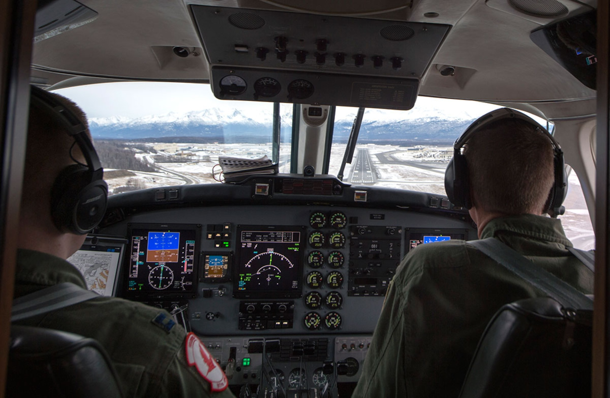 Maj. Ryan Wong, left, prepares to land at Joint Base Elmendorf-Richardson, Alaska, Feb. 23, 2016, while Lt. Col. Blake Johnson watches as part of site pilot training. Wong and Johnson are both assigned to the 517th Airlift Squadron. (U.S. Air Force photo/Staff Sgt. Sheila deVera)