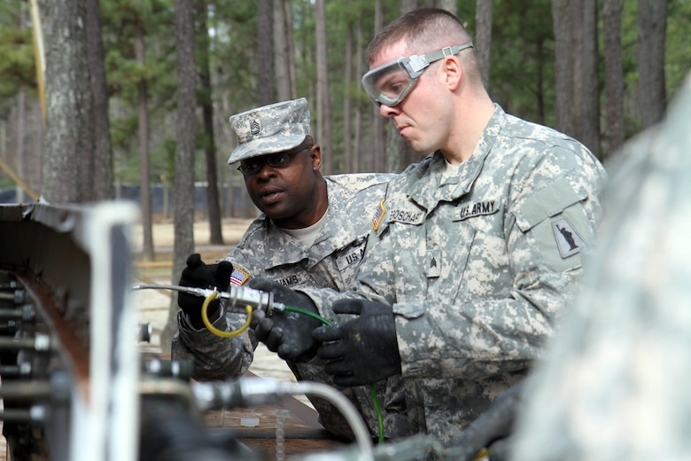 During a field training exercise for the Petroleum Supply Specialist Reclassification Course at Fort Lee, Va., Sgt. 1st Class Torron Williams, an instructor assigned to the 94thTraining Division, provides guidance to one of his students, Sgt. Taylor Broschart of the 947th Quartermaster Company out of Chambersburg, Penn.