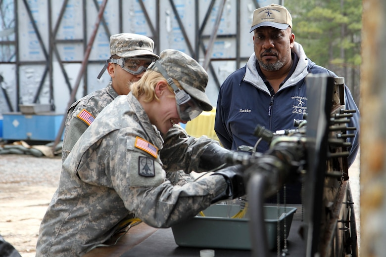 Russell Datts, civilian contractor and instructor at the 94th Training Division's Petroleum Supply Specialist Reclassification Course, tests Spc. Kirsten Gray and another student on fuel testing techniques in the field at Fort Lee, Va.