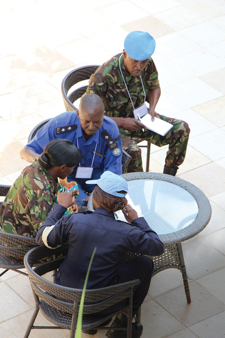 A small group of male and female Sierra Leonean security personnel work in their syndicate group in Freetown, Sierra Leone in November 2013.