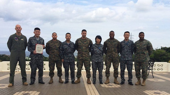 Members of the Japanese Air Self Defense Force pose with U.S. Marines for a photo at a farewell luncheon for the professional military exchange program February 23 at the Habu Pit Officers' Club on Marine Corps Air Station Futenma. The professional military exchange program benefits JASDF and Marines by providing first-hand insight to the daily routines and responsibilities of each service, according to Staff Sgt. Shinya Nishida, second from left. The experience and knowledge gained through the program establishes better understanding and communication. After Nishida's exposure to the Marine Corps, the JASDF will return the favor by taking in a Marine in March to experience day-to-day routines of the JASDF. Nishida was a participant of the program and is a flight plan dispatcher with the JASDF.
