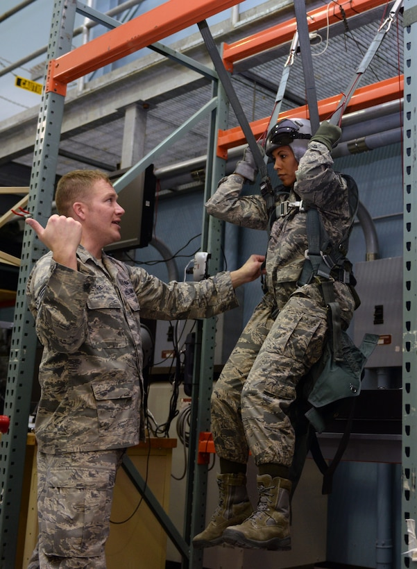 Staff Sgt. Dustin Jespersen, 28th Operations Support Squadron Survival, Evasion, Resistance, and Escape specialist, left, instructs Chief Master Sgt. Sonia Lee, 28th Bomb Wing command chief, on emergency parachute training at the SERE building at Ellsworth Air Force Base, S.D., Feb. 10, 2016. Ejection is a last resort for aircrew members who are trained to stay calm while ejecting and avoid tensing up when landing. (U.S. Air Force photo by Airman Donald C. Knechtel/Released)