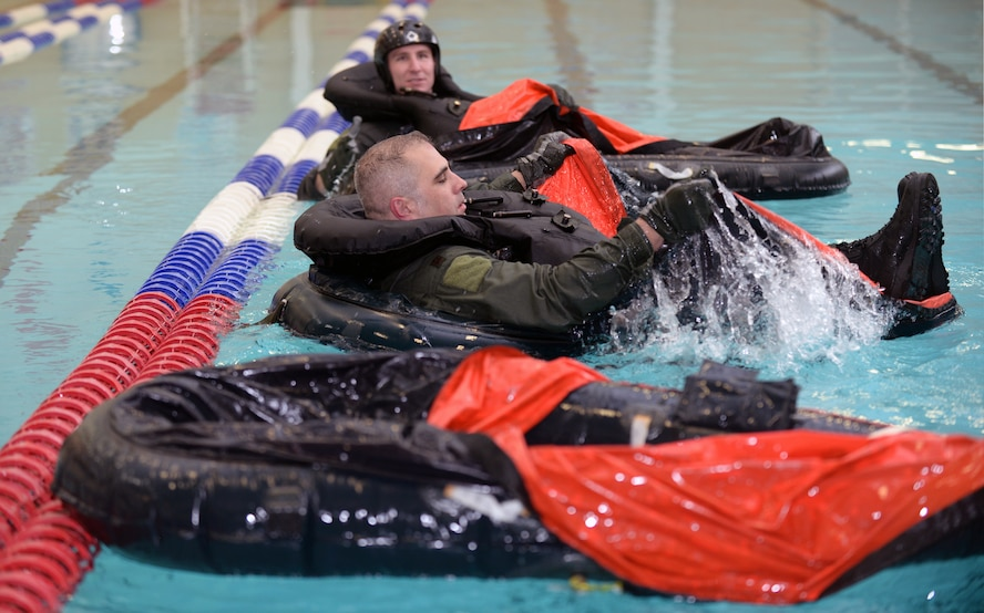 Maj. Daniel, 34th Bomb Squadron assistant director of operations, establishes himself in a deployable raft during Survival, Evasion, Resistance, and Escape training at the Bellamy Fitness Center indoor pool at Ellsworth Air Force Base, S.D., Feb. 9, 2016. Aircrew members learn various ways to mount the rafts depending on the situation in the event of emergency ejection over water, as well as how to establish themselves in the raft for long-term survival. (U.S. Air Force photo by Airman Donald C. Knechtel/Released)