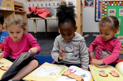 Three preschool students read books at the Child Development Center at Langley Air Force Base, Va., Feb. 16, 2016. The children received the books free of charge through The Mayor's Book Club, which provides community members an opportunity to promote affection for reading to preschool children. (U.S. Air Force photo by Airman 1st Class Kaylee Dubois/Released)