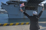 BUSAN, Republic of Korea (March 03, 2016) A Republic of Korea (ROK) Sailor waves the U.S. and ROK flags as USS Bonhomme Richard (LHD-6) pulls into ROK Fleet base. Bonhomme Richard is the flagship of the Bonhomme Richard Expeditionary Strike Group (ESG) 7 and is visiting Busan as part of a regularly scheduled port visit. (U.S. Navy photo by Mass Communications Specialist Jermaine M. Ralliford/RELEASED)