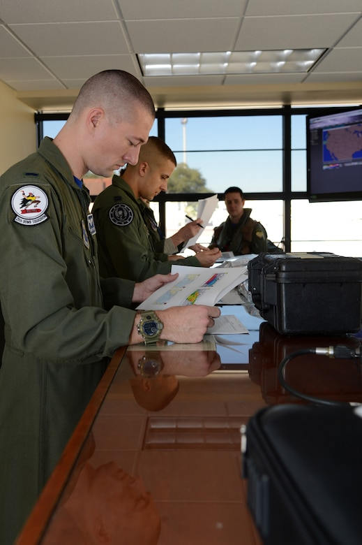 First Lt. Michael Totty, 20th Bomb Squadron, receives a pre-flight brief at Barksdale Air Force Base, La., Feb. 26, 2016. Aircrew and three B-52 Stratofortress heavy bombers departed Barksdale to participate in Exercise Cold Response 16 at Moron Air Base, Spain. CDR16 is a combination of Norwegian joint command post and field training exercises between NATO allies and partners from 13 nations running from Feb. 29 to March 9. (U.S. Air Force photo/Staff Sgt. Joseph A. Pagán Jr.)