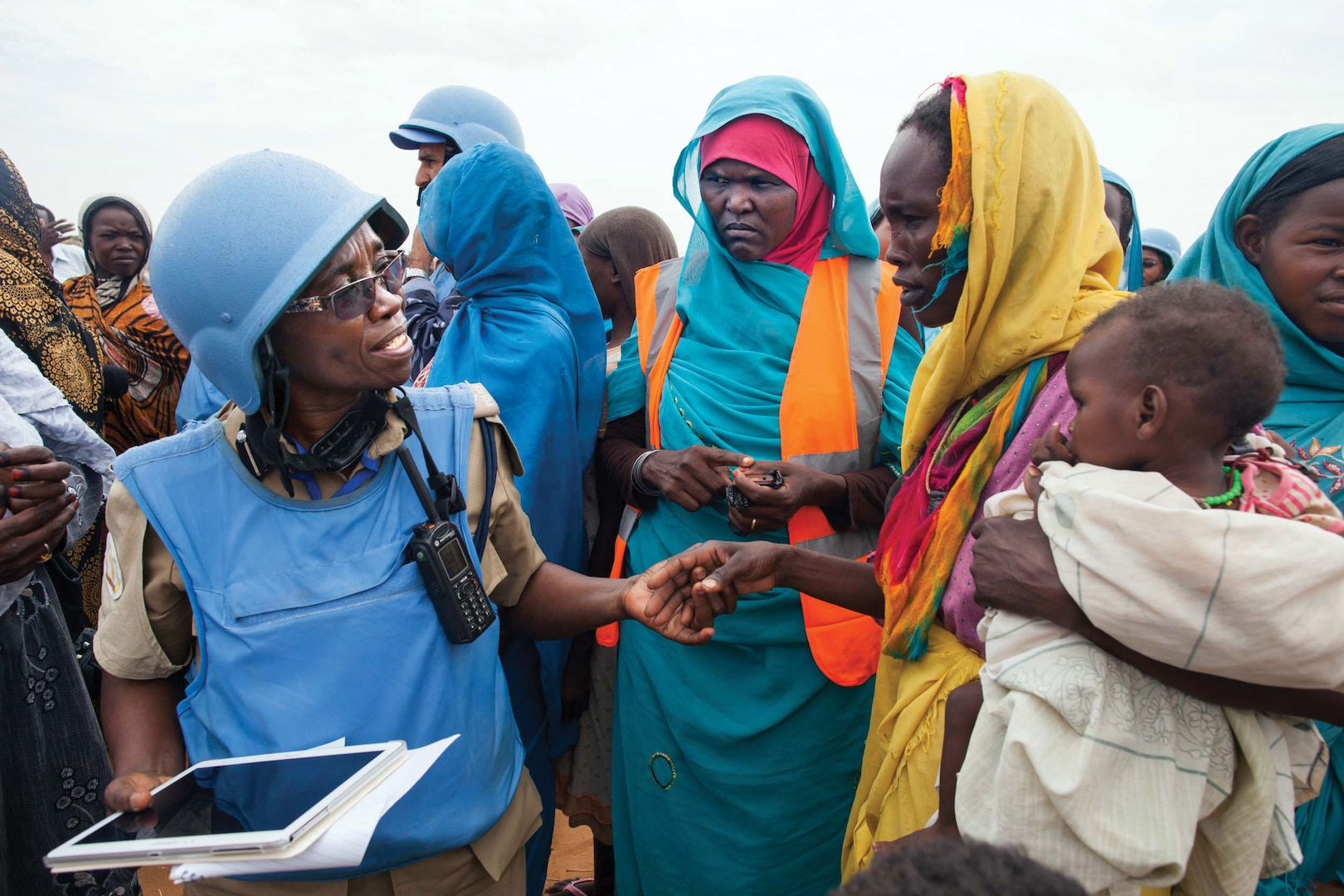 Community policing volunteers bridge divides in Darfur. In the Zam Zam camp for Internally Displaced People in North Darfur, UNAMID police officer Grace Ngassa, from Tanzania (left), and Community Policing Volunteer Jazira Ahmad Mohammad (center) interact with a woman and her child (right).